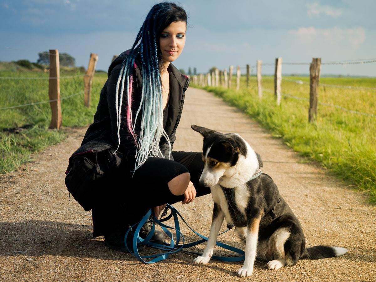 Frau mit Dreads in Hocke mit Hund auf Weg Stellenwert Hund