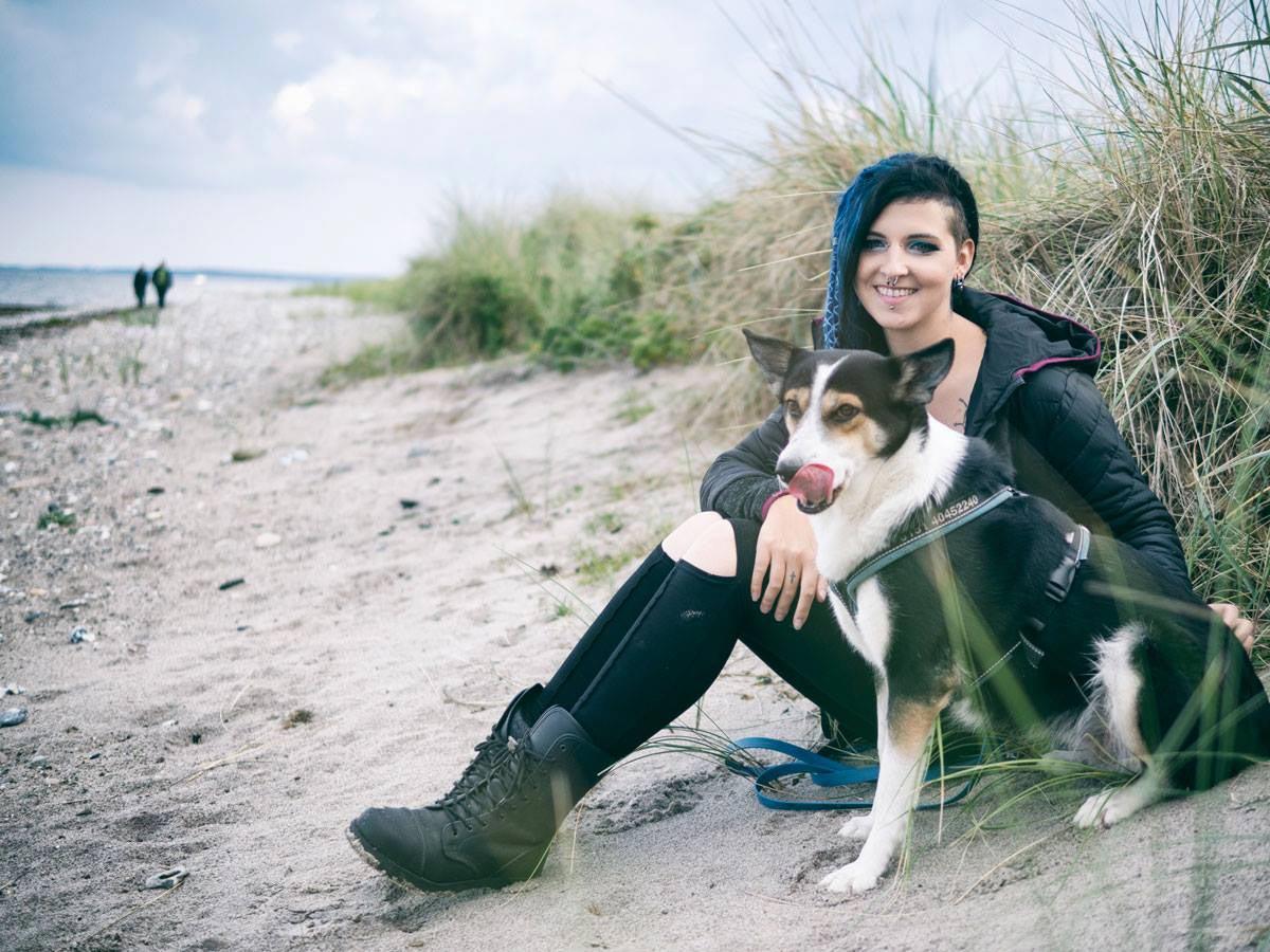 Frau mit Hund sitzend am Strand